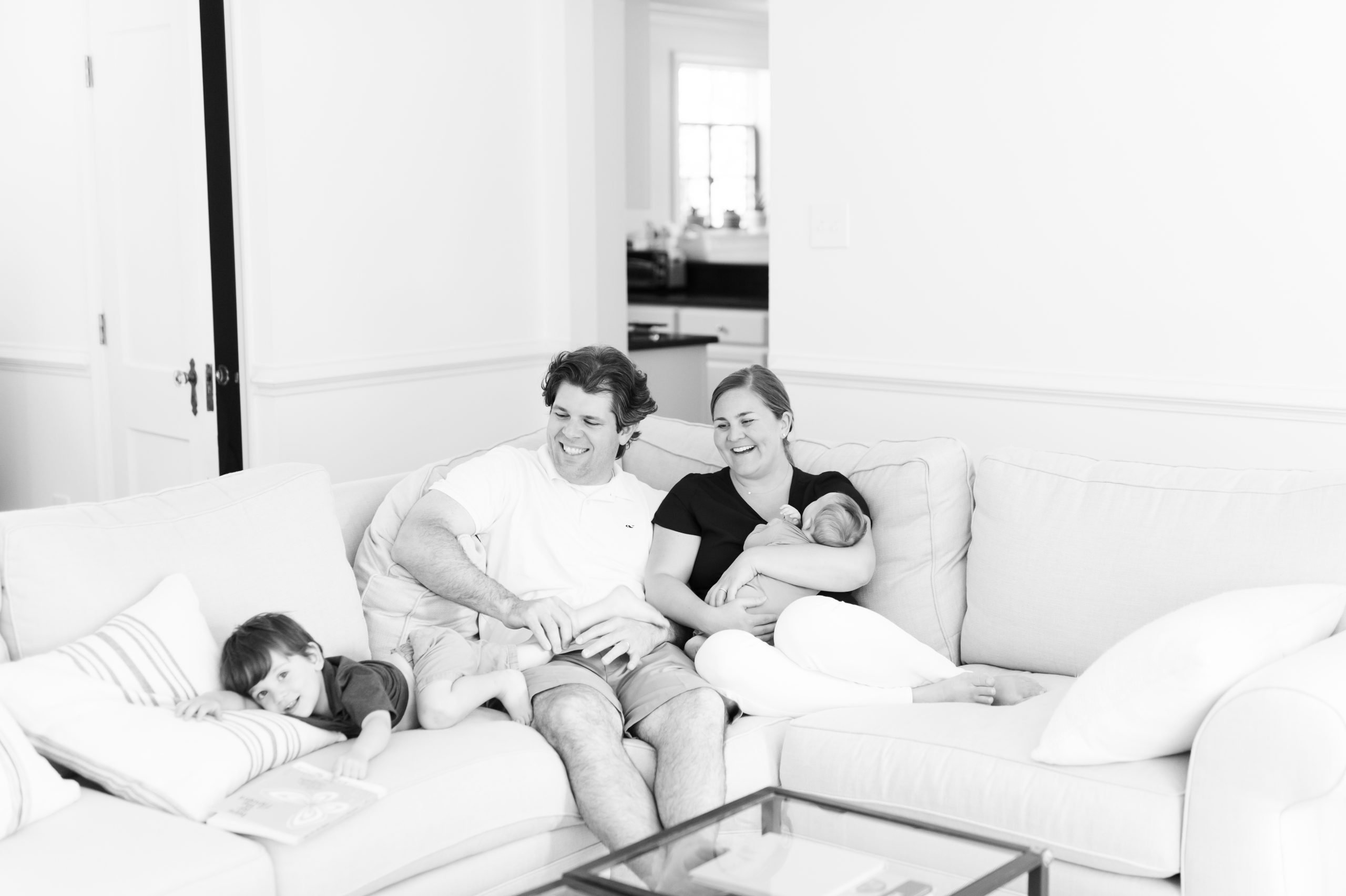 family wiht newborn sitting on couch