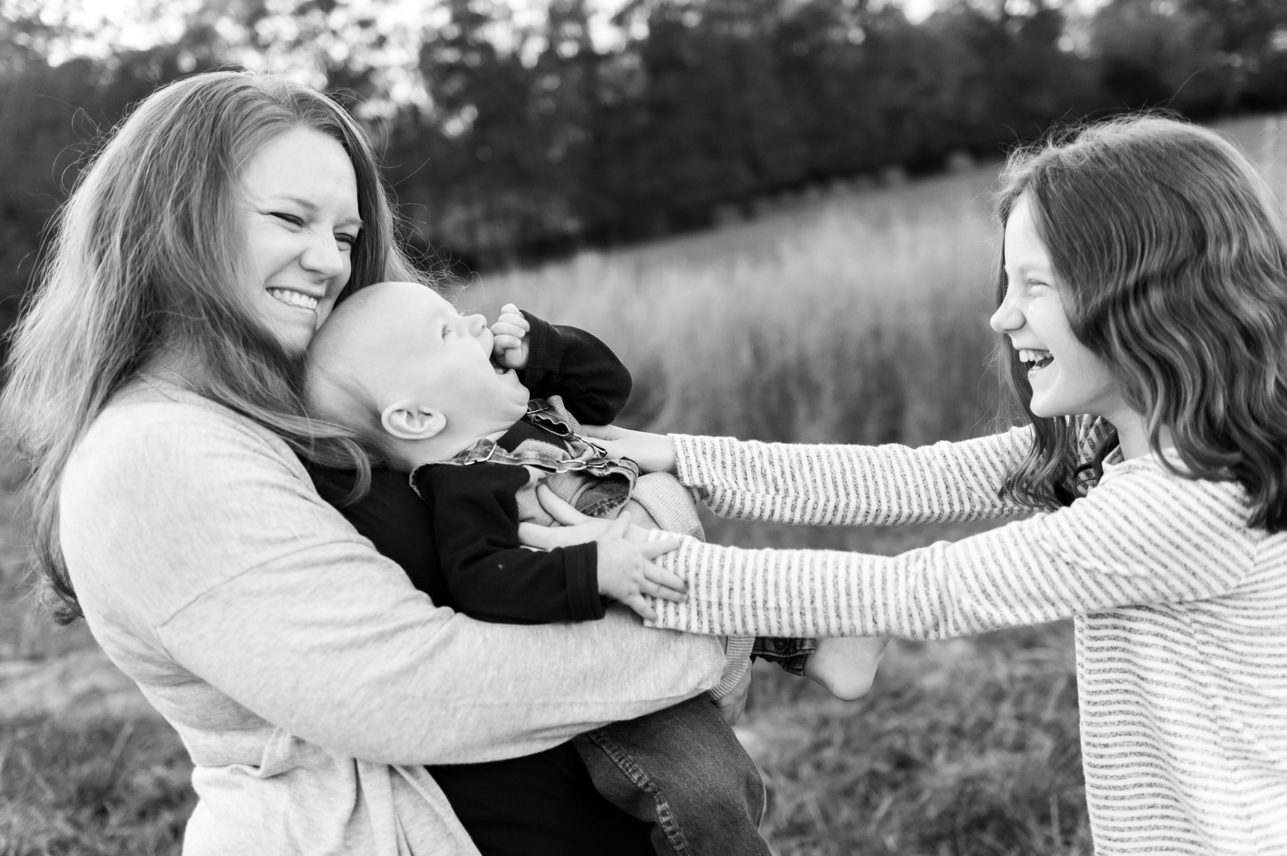 mother holding baby and laughing with older daughter