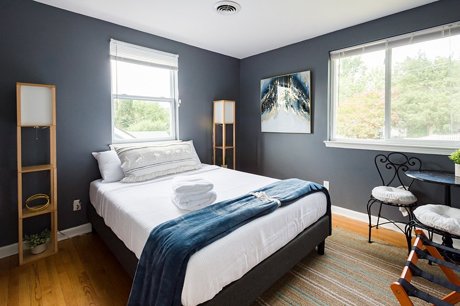 grey bedroom with a well made bed