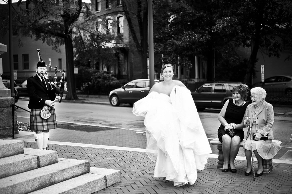 bride wlaking down the street to go to church and a bagpiper playing