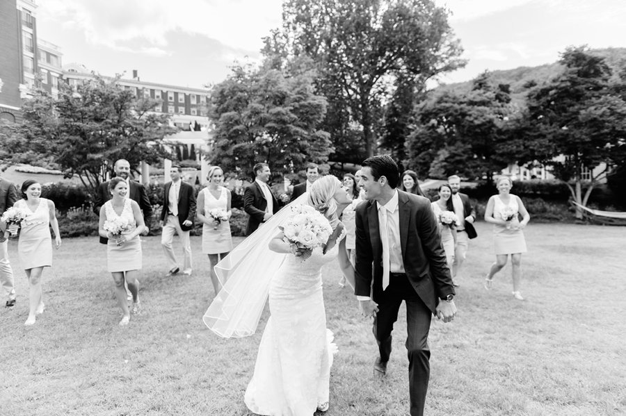 newly wed kissing and laughing while walking