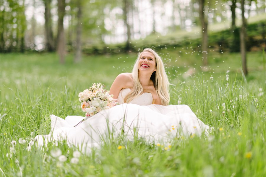 bride sitting in the grass with bouquet